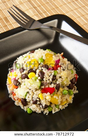Quinoa salad with colorful vegetables on a black plate
