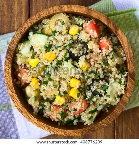 Quinoa salad with sweet corn, olive, tomato, cucumber and chives in wooden bowl, photographed overhead with natural light (Selective Focus, Focus on the top of the salad)