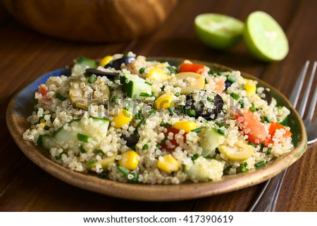 Quinoa salad with sweet corn, olive, tomato, cucumber and chives on plate, photographed on dark wood with natural light (Selective Focus, Focus in the middle of the salad) - stock photo