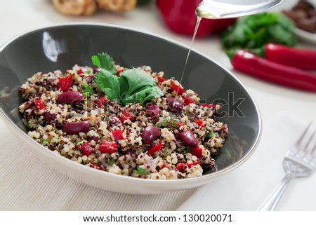 Quinoa salsa with capsicum, onions and beans covered in olive oil - stock photo