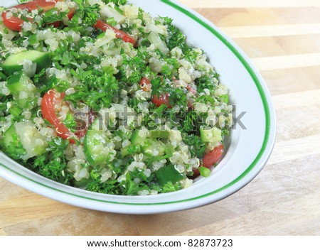 Quinoa Tabouleh salad in a bowl sitting on a wooden table. - stock photo