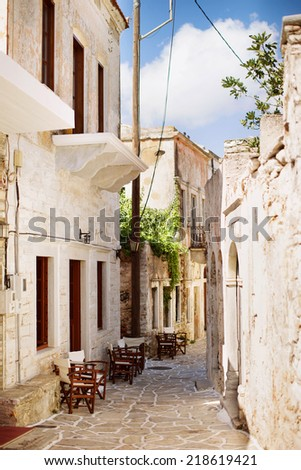 Quirky old street on Naxos Island, Greece in the village of Halki. Features chairs for gathering and a closed restaurant.