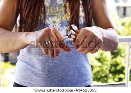 Quit smoking cigarettes. A young girl breaks a cigarette - stock photo