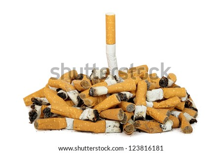 quit smoking concept with whole cigarette among cigarette butts - stock photo