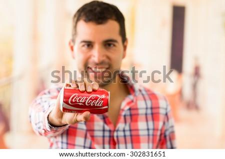 QUITO, ECUADOR - AUGUST 3, 2015: Attractive young man smiling holding a Coca-Cola can - stock photo