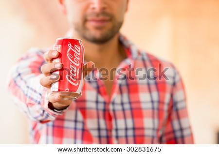 QUITO, ECUADOR - AUGUST 3, 2015: Closeup of young man holding a Coca-Cola can - stock photo