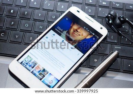 QUITO, ECUADOR - AUGUST 3, 2015: White smartphone closeup lying next to silver pen on laptop keyboard with Mark Zuckerberg Facebook profile screen visible. - stock photo