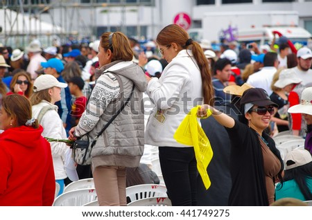 QUITO, ECUADOR - JULY 7, 2015: Women waitting to see pope Francisco mass event, one with her mobile phone and other with a yellow flag