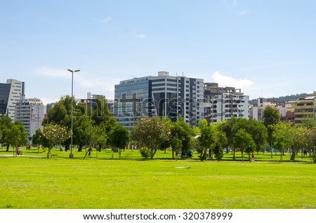QUITO, ECUADOR- MARCH 20, 2015: Inside La Carolina park in Quito, Ecuador. Beautiful green outdoors with some tall office buildings marking the city presence. - stock photo