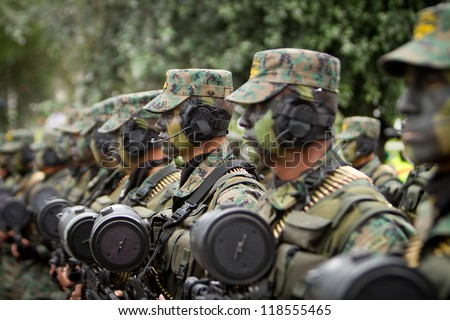 QUITO, ECUADOR- MAY 24:  National  military parade, unidentified camouflage row of soldiers with army and military gear. May 24, 2012, Quito, Ecuador - stock photo