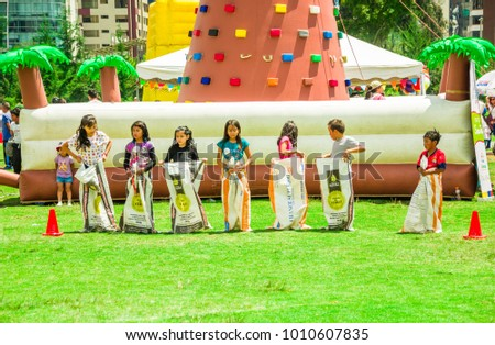 QUITO, ECUADOR- NOVEMBER, 28, 2017: Outdoor view of many children playing inside of sacks during a foam festival in a carolina park in a sunny day