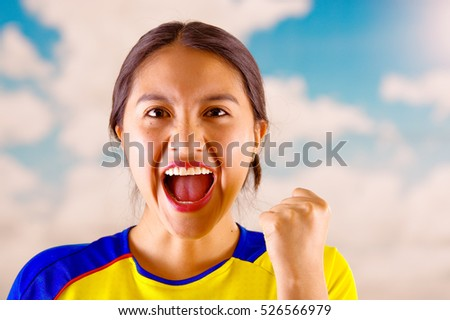QUITO, ECUADOR -8 OCTOBER, 2016: Young ecuadorian woman wearing official Marathon football shirt standing facing camera, very engaged body language watching game with great enthusiasm, blue sky and