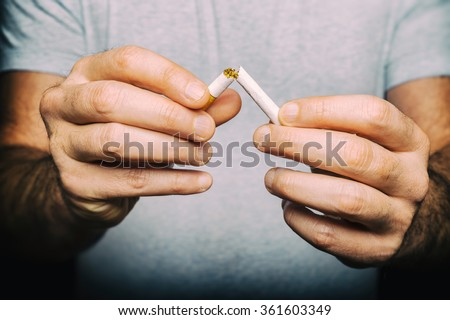 Quitting smoking - male hand crushing cigarette - stock photo