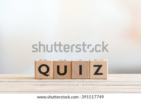 Quiz sign made of wood on a wooden table - stock photo