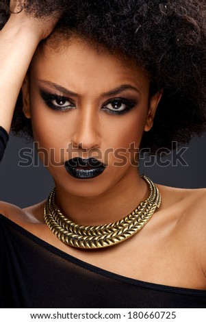 Quizzical beautiful elegant African American woman frowning as she looks at the camera with an intense expression and a raised eyebrow - stock photo