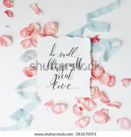 "quote ""Do small things with great love"" written in calligraphy style on paper with pink petals and blue ribbon. Flat lay, top view"