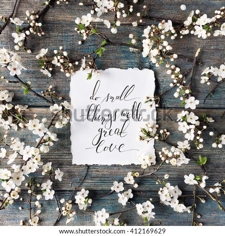 "quote ""Do small things with great love"" written in calligraphy style on paper with wreath frame of flowers and branches isolated on retro wooden mint table background. flat lay, overhead top view - stock photo"