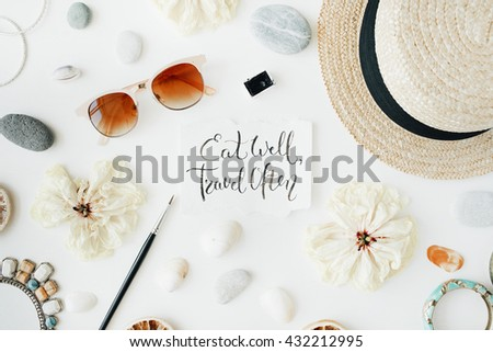 quote eat well travel often written in calligraphy style with straw, sunglasses, female accessories and dry white tulips on white background - stock photo