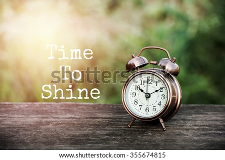 quote time to shine on image vintage alarm clock on table with blur green background and sunray - stock photo