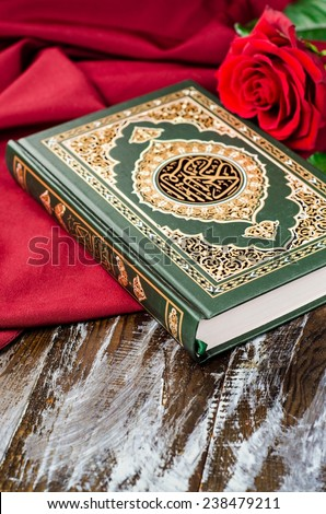Quran - holly book of Islam with rose and red scarf on wooden background. Selective focus - stock photo