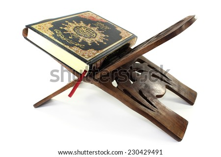 Quran with Quran wooden stand in front of white background - stock photo