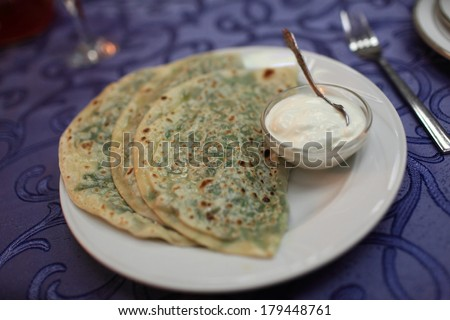 Qutab with greens on a white plate - stock photo