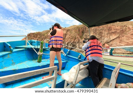 Quy Nhon City, Binh Dinh Province, Vietnam - August 28, 2016: tourists are trying to take a picture on wooden boat traveling KyCo Island, Binh Dinh Province, Vietnam