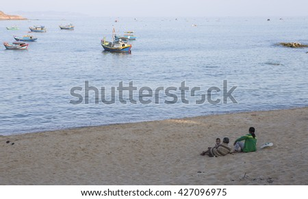 Quy Nhon, Vietnam - Apr 20, 2016: Fisherman family relax on the beach and watching fishing boat returning to the harbor at sunset in the end of the day.