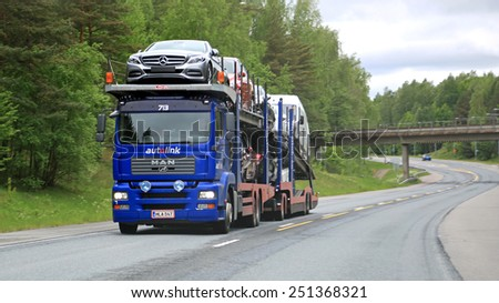 RAASEPORI, FINLAND - MAY 31, 2014: MAN car carrier hauls a load of new cars. The Finnish automotive industry estimates that a total of 109,000 new passenger cars will be sold in Finland in 2015. - stock photo
