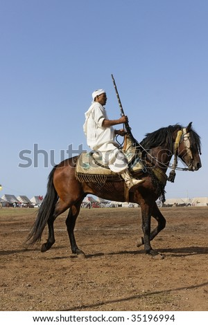 RABAT, MOROCCO - JULY 30: Local rider participates in a traditional fantasia event (or MOUSSEM in Arabic) which is mainly a hobby and a sport July 30, 2009 in Rabat, Morocco. - stock photo