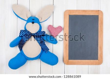 Rabbit, heart, blackboard on white wood background - stock photo
