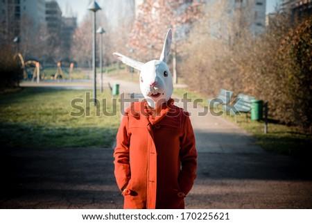 rabbit mask woman red coat winter desolate landscape - stock photo