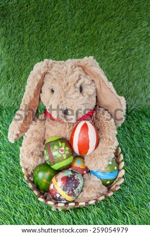 Rabbit, sit and holding colorful eggs in basket on grass for happy easter festival, top view - stock photo
