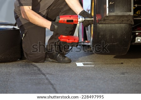 Race car being serviced with new slick tires by a mechanic during a race in the pit lane - stock photo