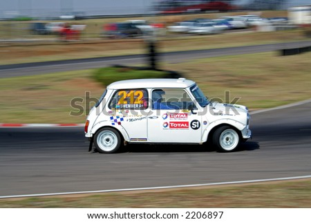 Race car busy racing around a track - stock photo
