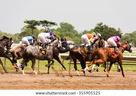 Race horses galloping at the track - stock photo