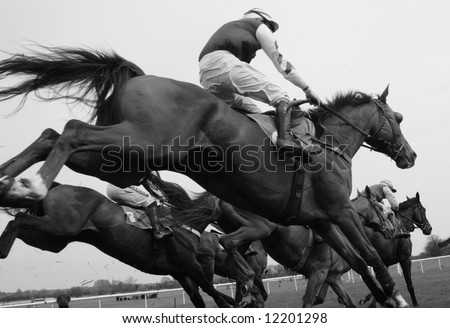 race horses jumping fence from below - stock photo