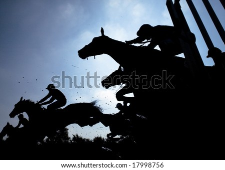 race horses jumping over a hurdle at speed photographed in silhouette - stock photo