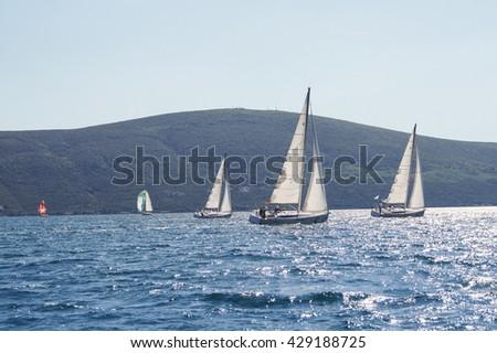 "Race yacht to the shore. Tivat, Montenegro - 26 April, 2016. Regatta ""Russian stream"" in God-Katorskaya bay of the Adriatic Sea off the coast of Montenegro. - stock photo"