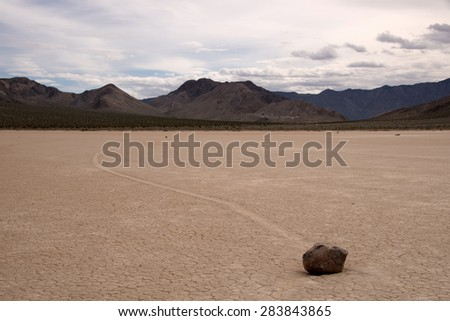Racetrack Playa is a seasonally dry lake (playa) located in the northern part of the Panamint Mountains that is famous for rocks that mysteriously move across its surface. - stock photo