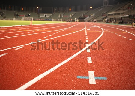racetrack, red rubber racetracks in big stadium evening - stock photo