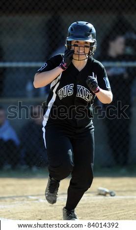 RACHEL, WV - APRIL 21: A North Marion HS (WV) softball player runs to first base after making contact in a game against Cameron April 21, 2011 in Rachel, WV. - stock photo