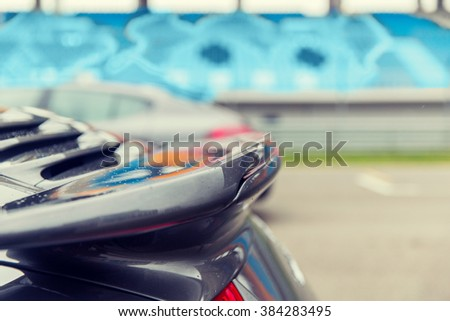 racing, motosports, extreme and motoring concept - close up of sports car back spoiler on speedway of stadium - stock photo