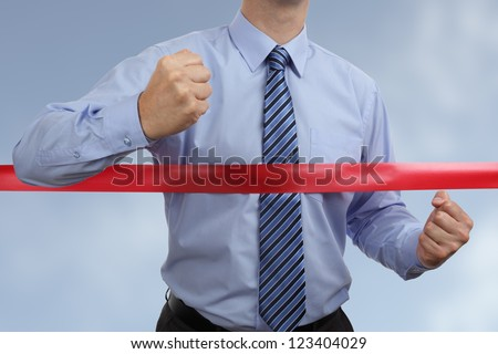 Racing to first place at the red ribbon finish line concept for winning and success - stock photo