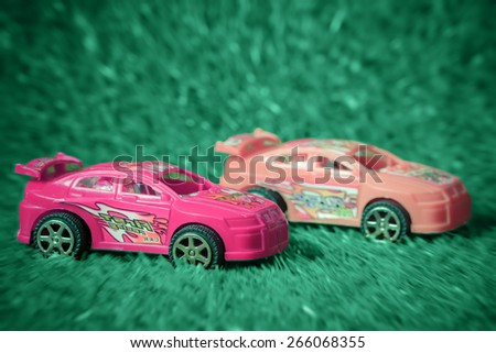Racing toy car on pastel style grass made with effect radial zoom - stock photo