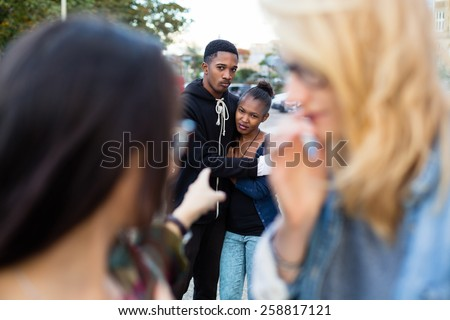 Racism - black couple being bullied, people pointing with finger on them - stock photo