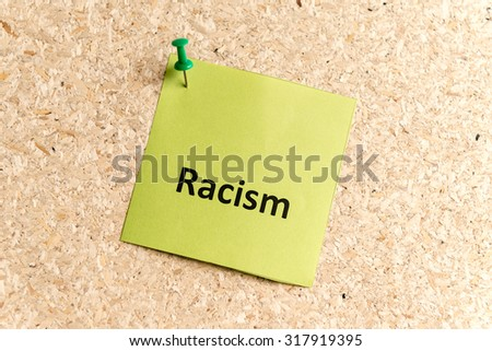 racism word typed on a paper and pinned to a cork notice board - stock photo