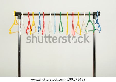 Rack of clothes with empty hangers. Colorful plastic hangers on display. - stock photo