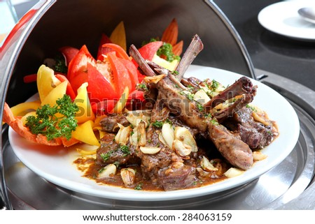 Rack of lamb grilled with garlic, vegetables and sauce - stock photo
