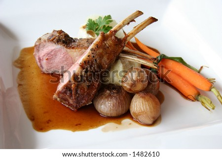 Rack of lamb with pickled poached onions, grapefruit and baby carrots - stock photo